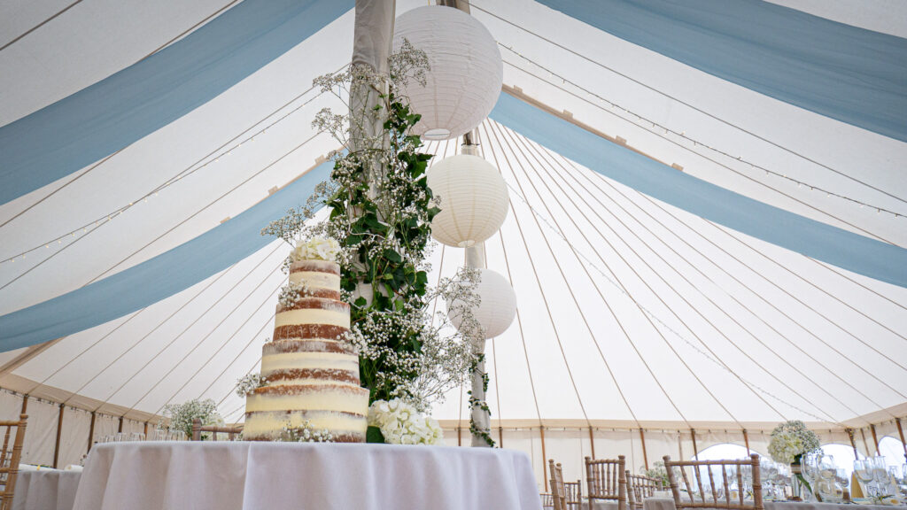 a semi-naked wedding cake in a marquee