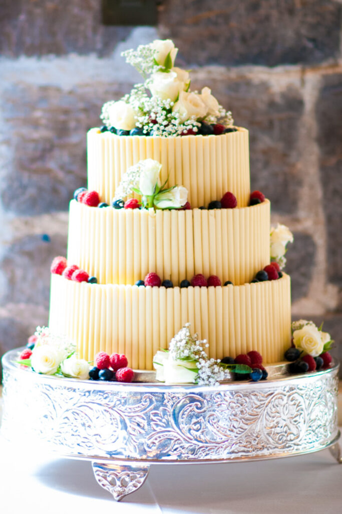 a three tier wedding cake with white chocolate curls around the sides