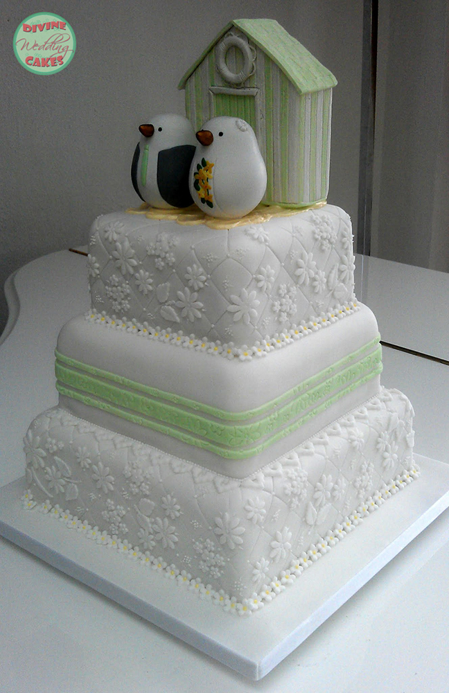 a wedding cake with lace and a beach hut seaside theme