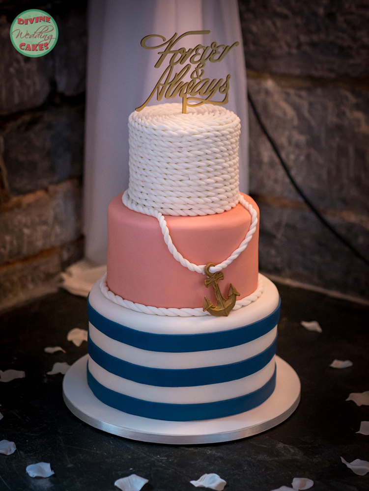a three tier wedding cake with a nautical theme