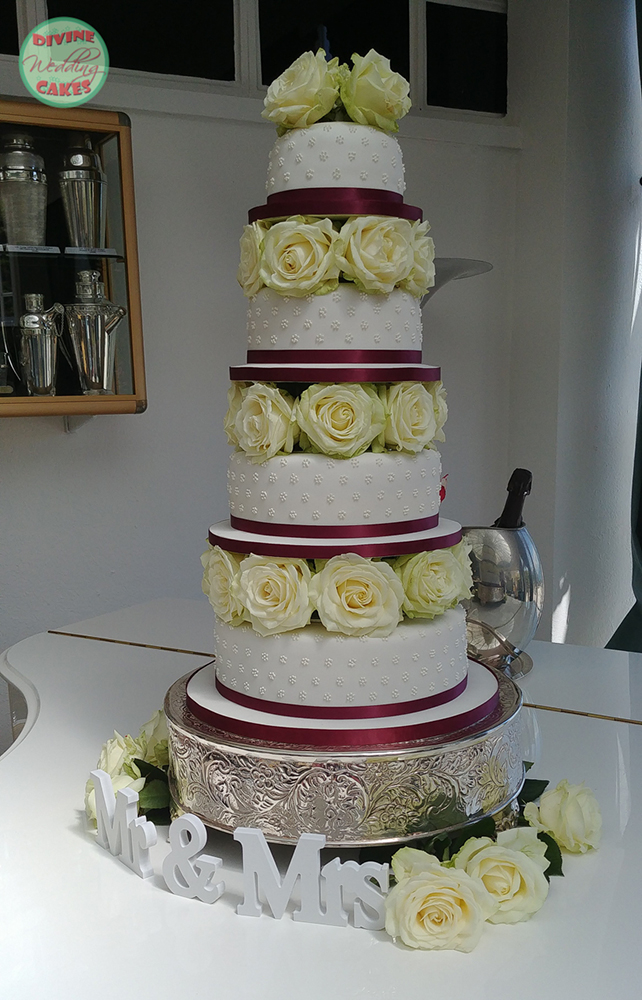 Iced cake stacked with fresh roses