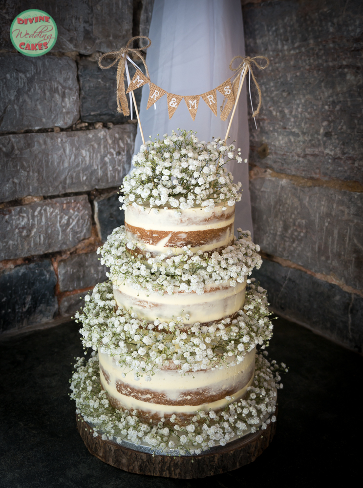 A semi-naked wedding cake with gypsophila and bunting