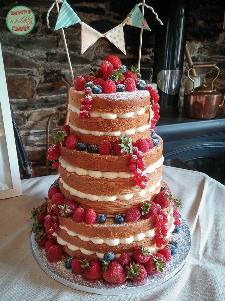 a naked wedding cake with berries and bunting