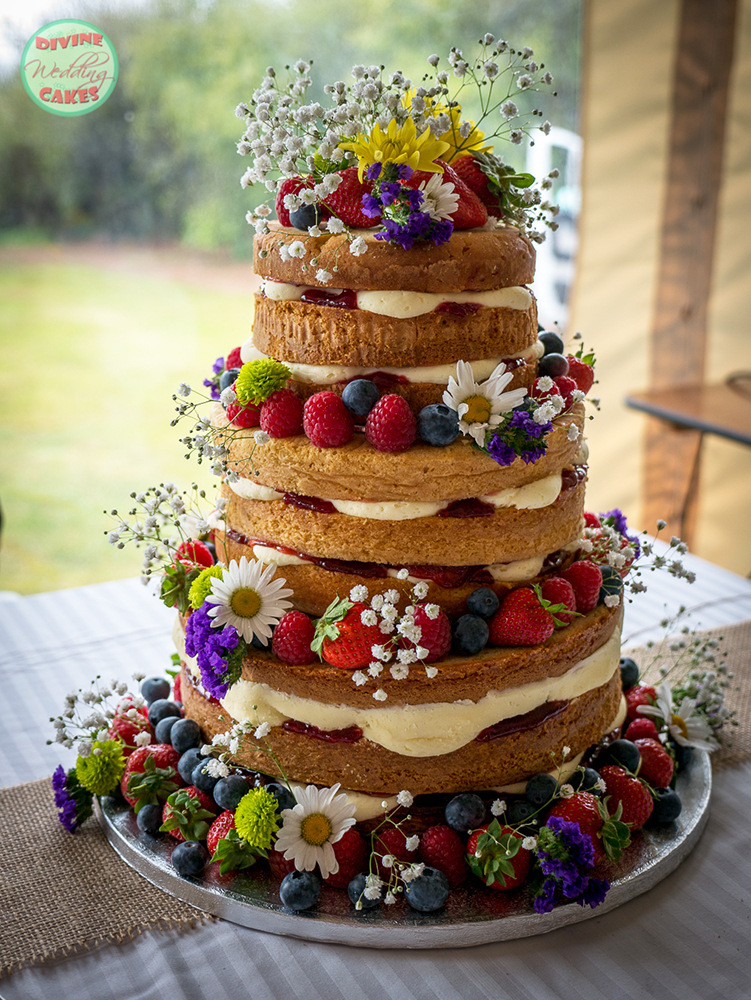 a naked wedding cake with berries and fresh flowers