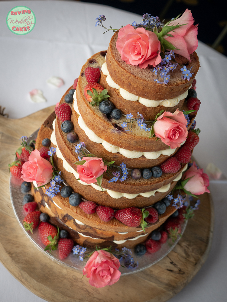 a naked wedding cake with berries, roses and forget-me-nots