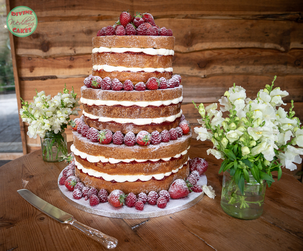 a naked wedding cake with strawberries and raspberries