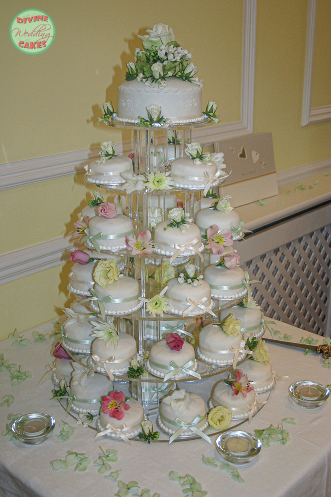 a tower of mini wedding cakes with fresh flowers