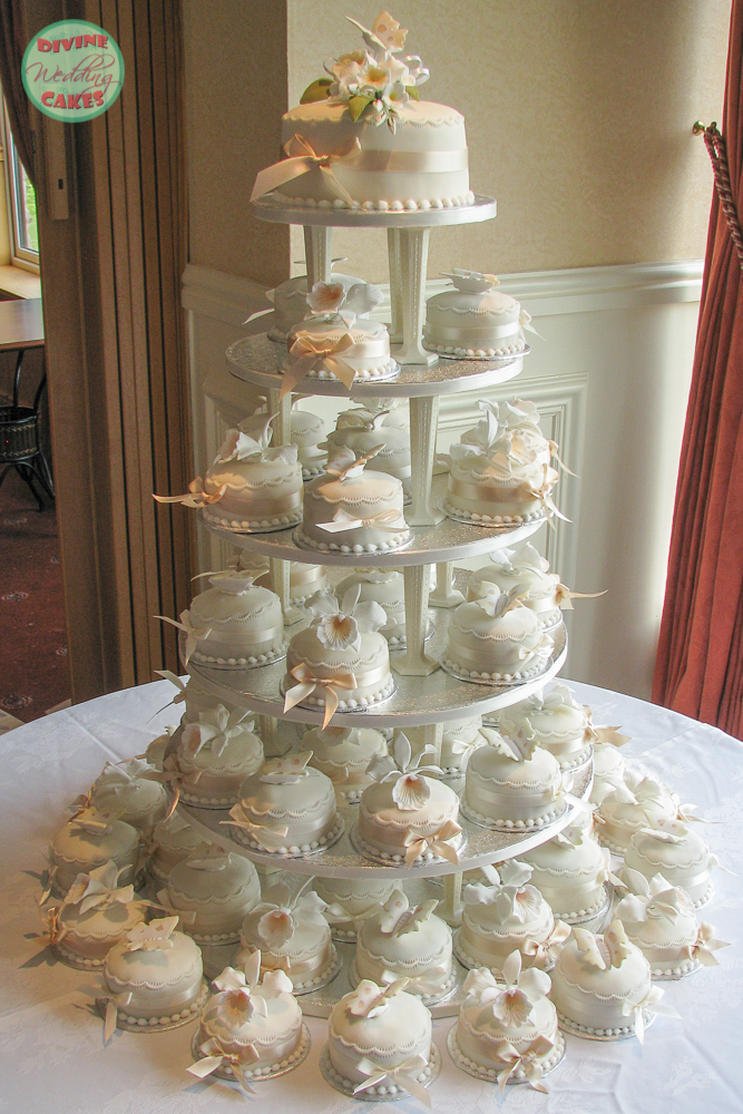 a tower of mini wedding cakes with sugar flowers on top